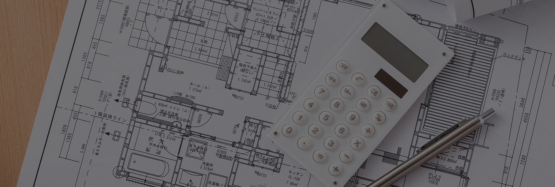 写真:設計図の上に置かれたペンと電卓